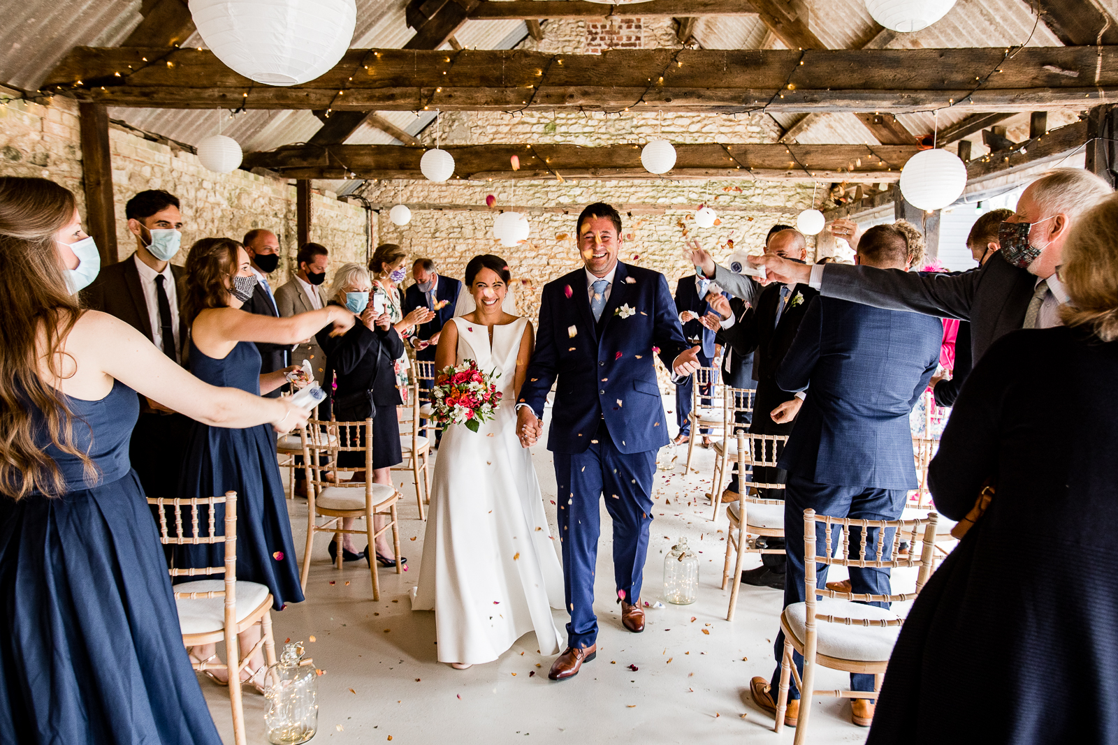 Wedding ceremony in rustic barn at East Afton Farmhouse, with guests wearing masks
